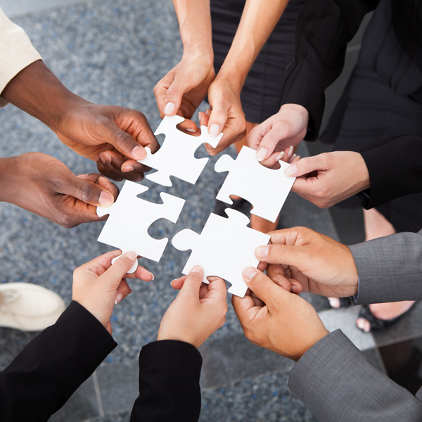 Group of hands holding puzzle pieces
